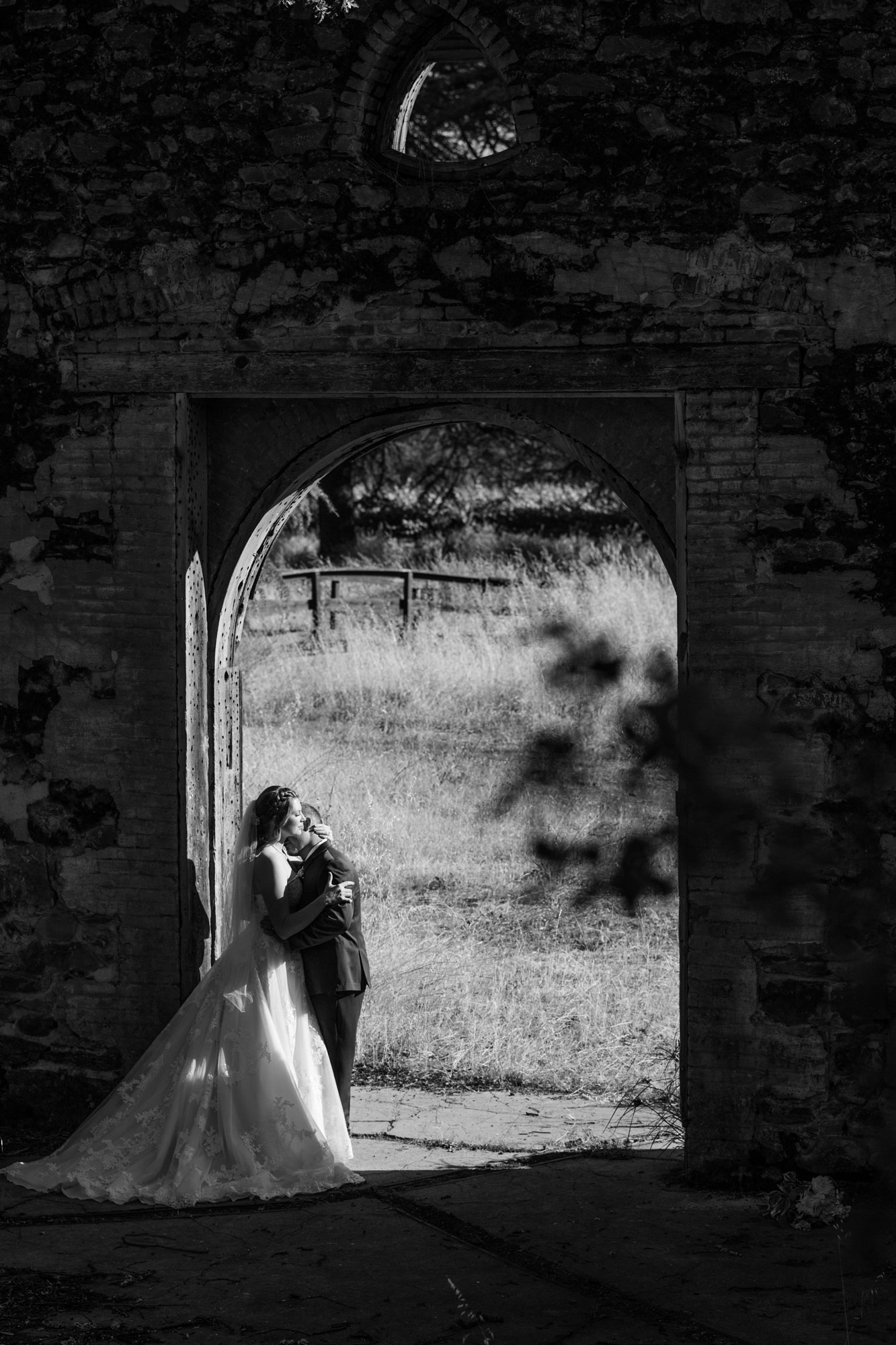 Black and white photo of bride and groom standing in an abandon doorway