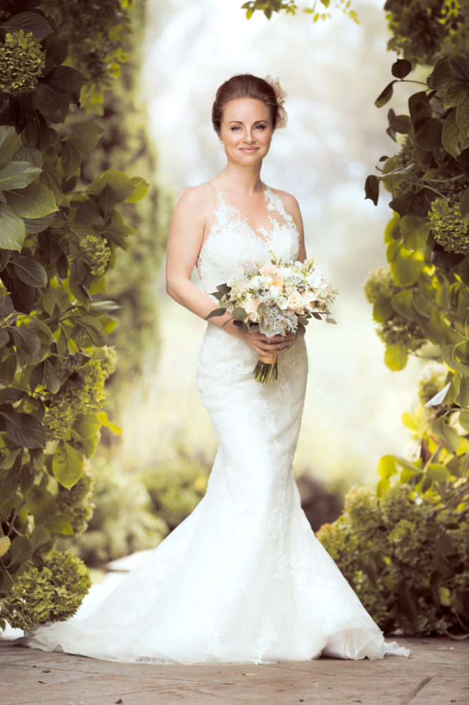 Full lenght wedding portrait of woman holding a bouquet among greenery.