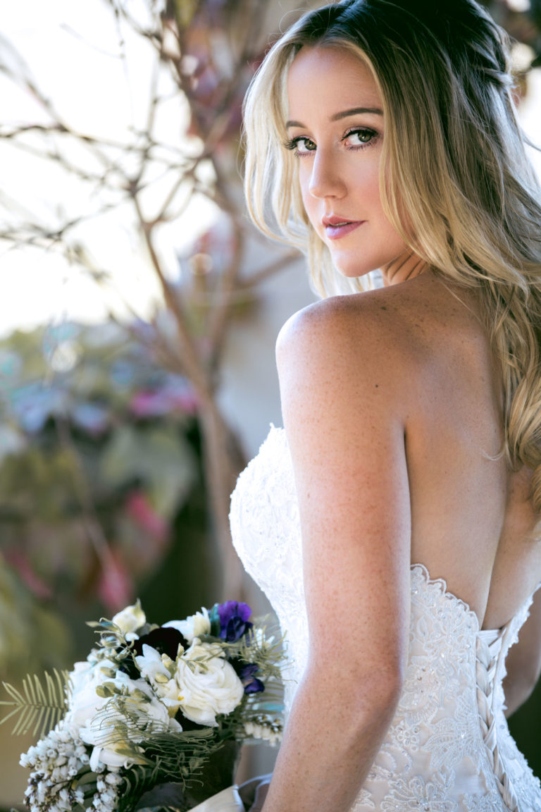 Portrait of a bride looking over her shoulder while holding her bouquet