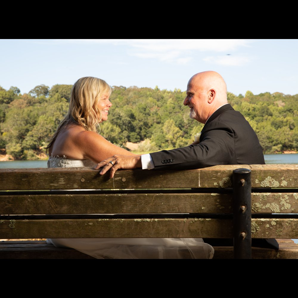 Bride and groom sit on bench overlooking lake.