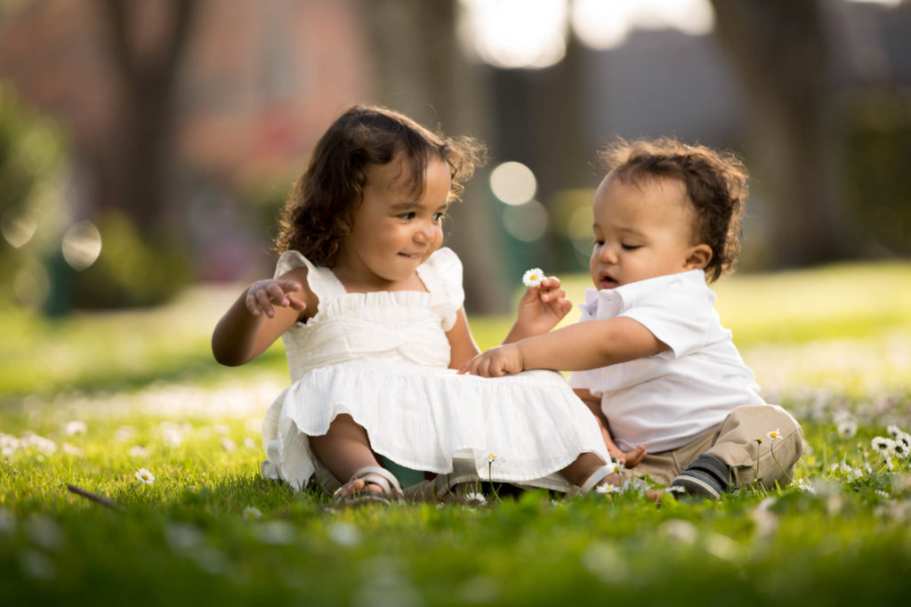 Children's portraits of a brother and sister sitting on the grass among the daisy's in a park