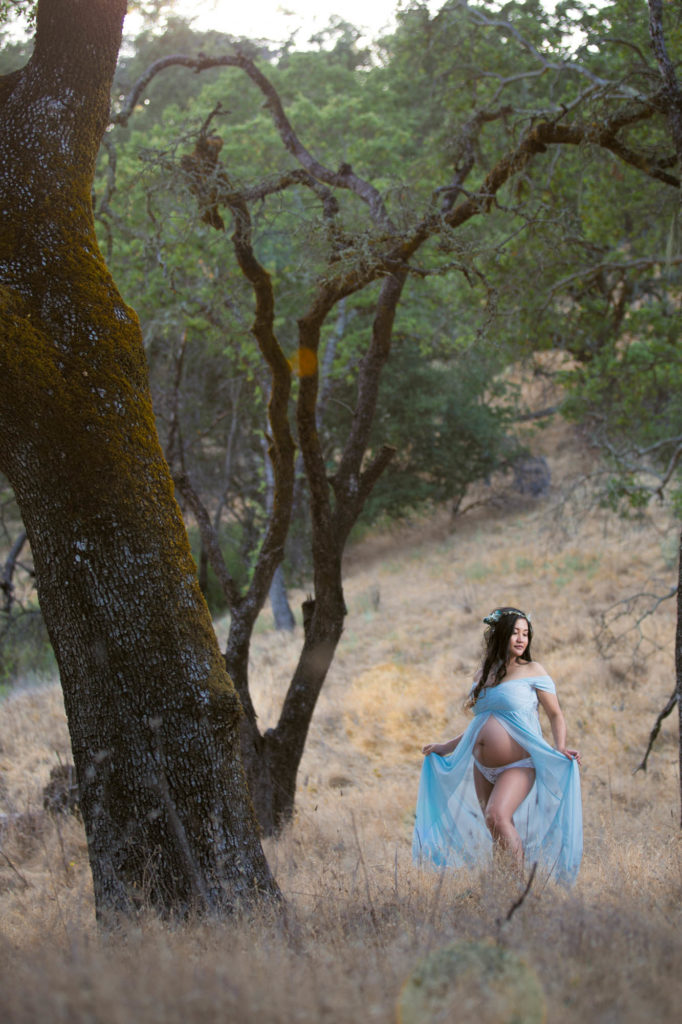 Outdoor enviornmental portrait of a pregnant woman wearing a blue dress standing in an oak forest