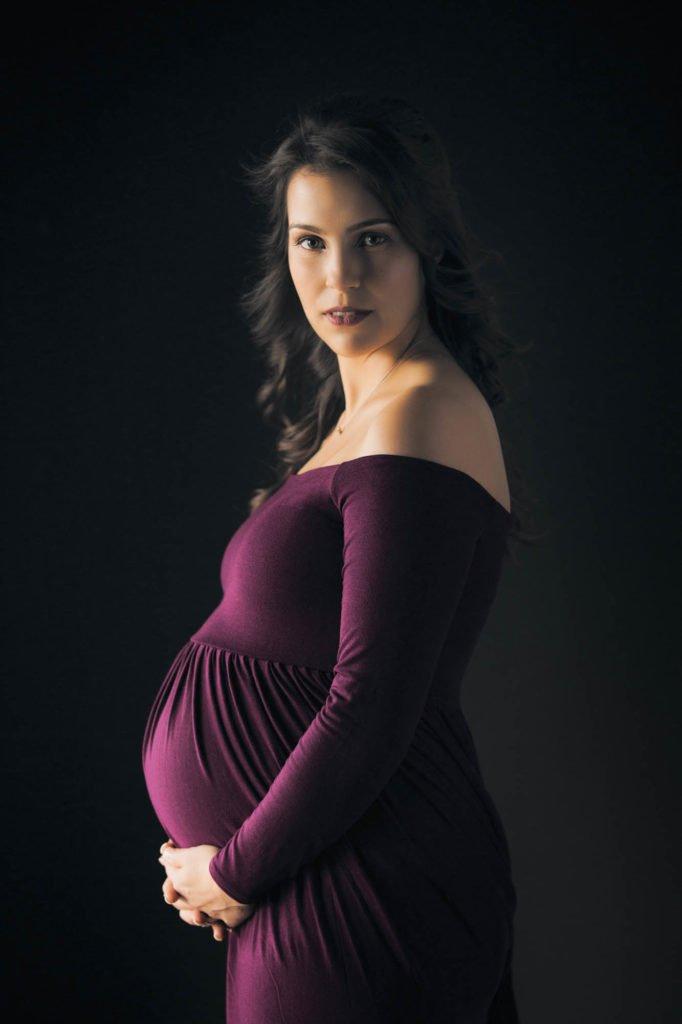 Maternity portrait of woman in purple dress on black background