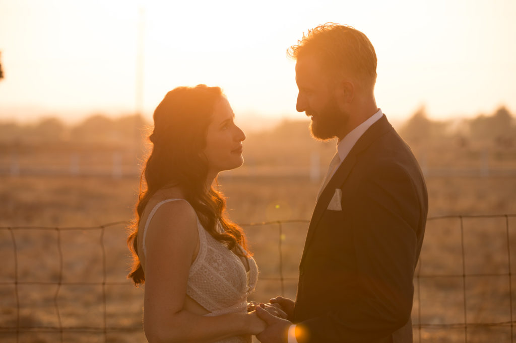 Newly wed couple holding hands at sunset