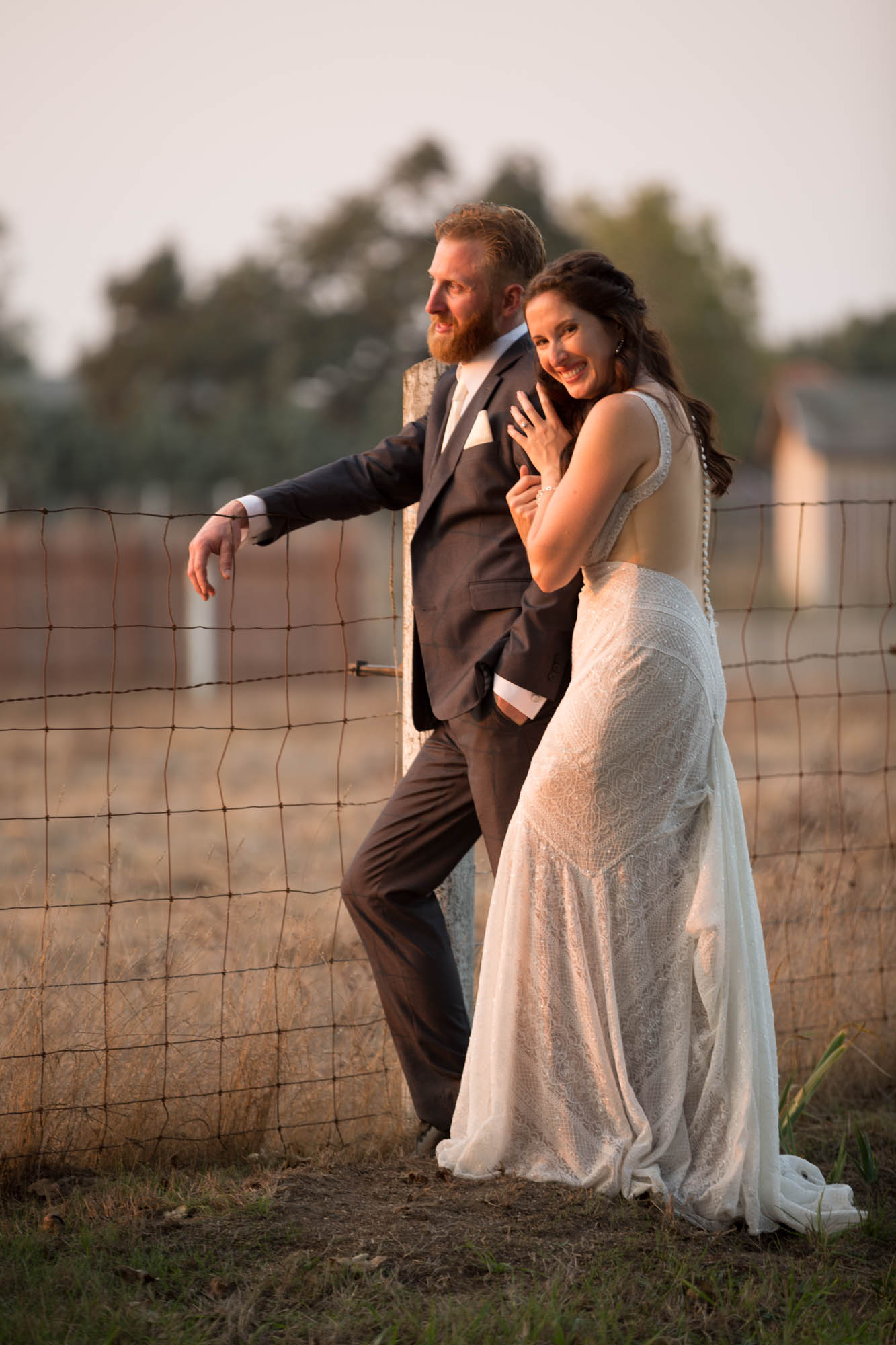 Bride hugs grooms arm while he leans on a country fence