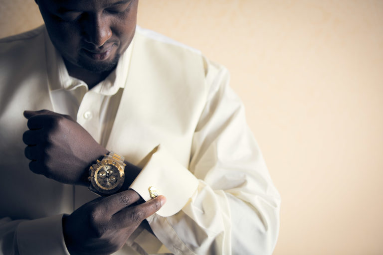 Groom putting on cuff links as he get's ready for wedding.