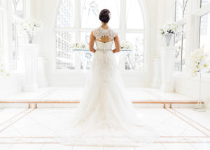 Bride standing at bright white church alter in her wedding dress
