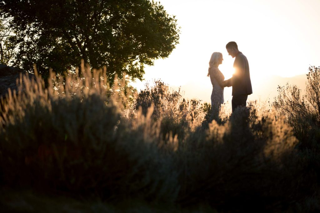 Silhouette of bride and groom at sunset in a field