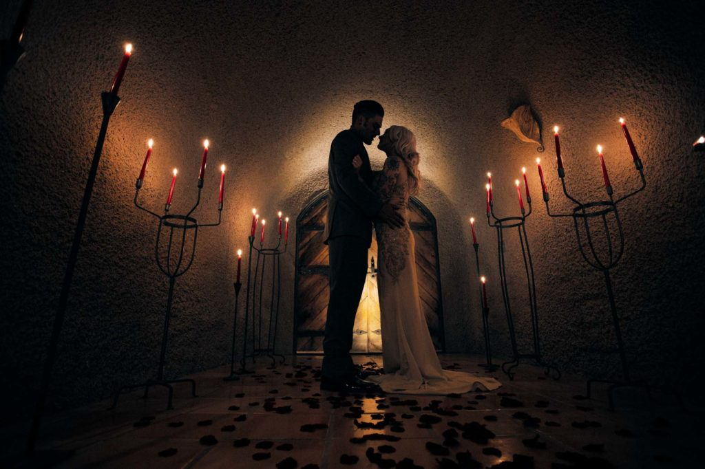 Wedding couple embraces in wine cave surrounded by candles.