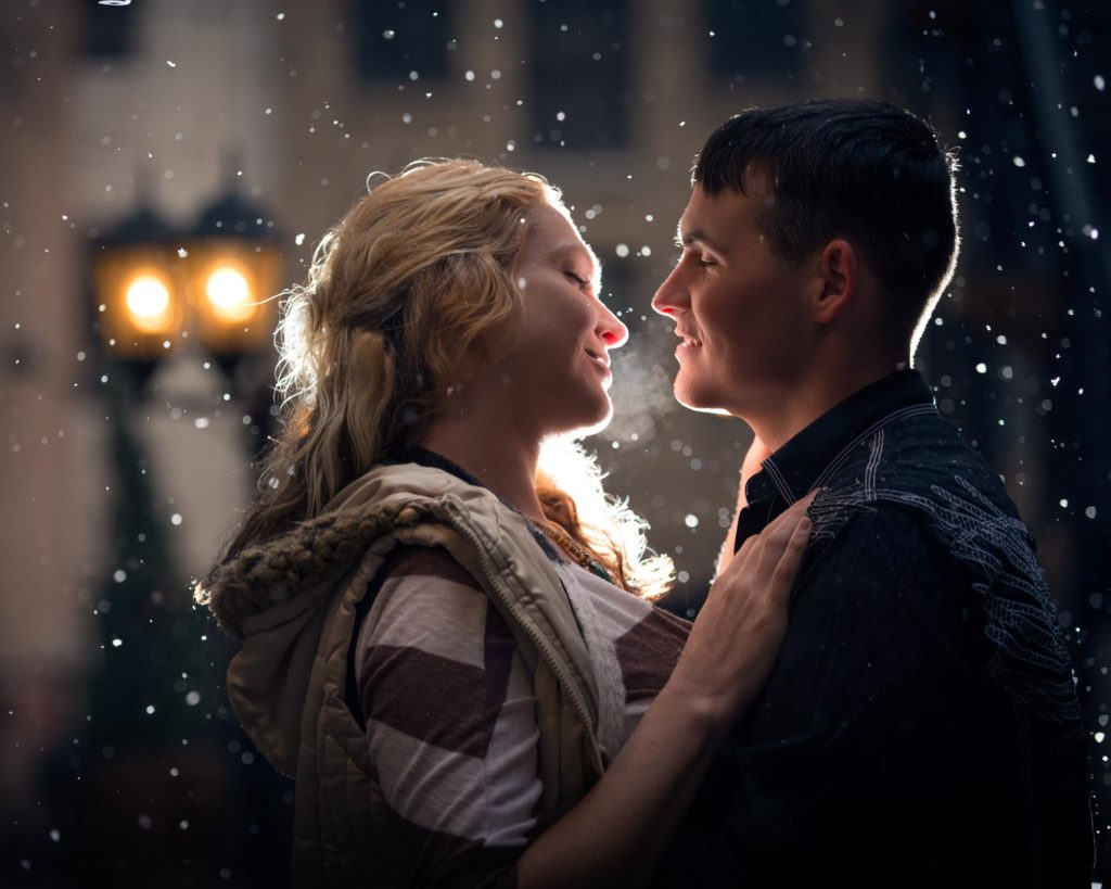Couple's portrait on a snowy evening in the park