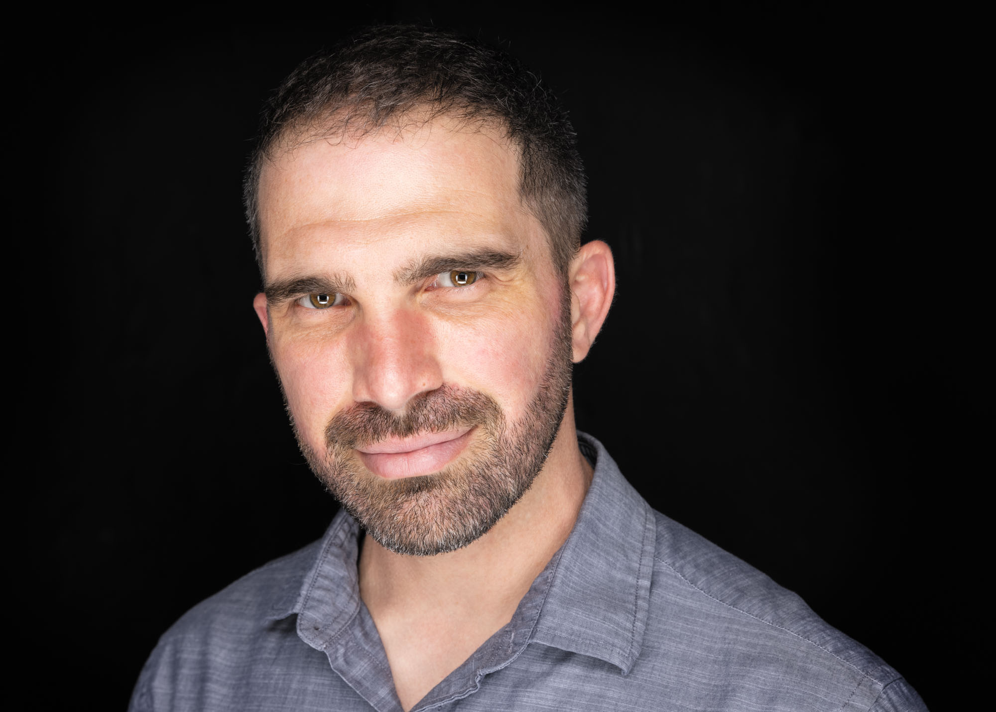 Headshot of portrait photographer Jason Guy on black background
