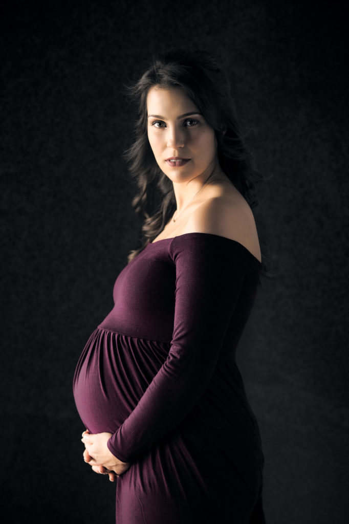 Maternity photo of a woman in a purple dress on black background