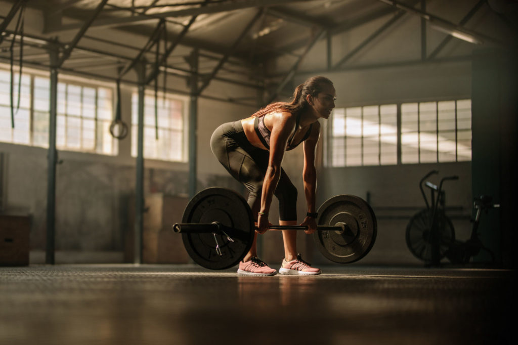Fit young female athlete lifting heavy weights and Losing Weight For Wedding