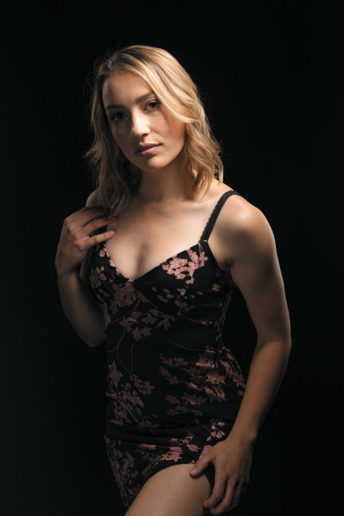 garage photo shoot featuring a woman in a flower dress on a black background